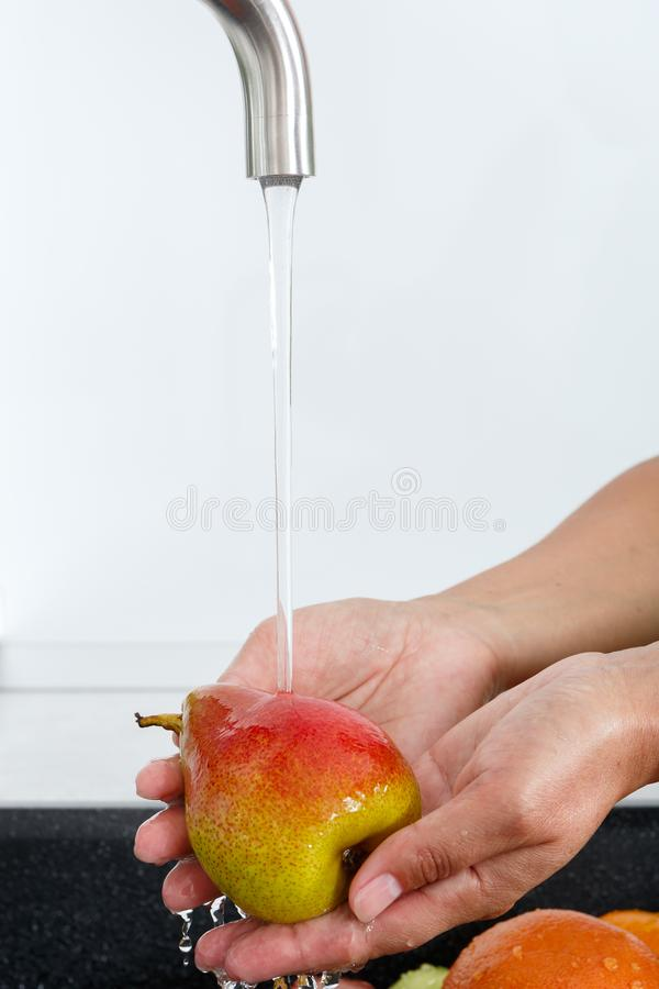 De kokvrouw wast een peer onder het water die van een waterkraan stromen royalty-vrije stock foto's