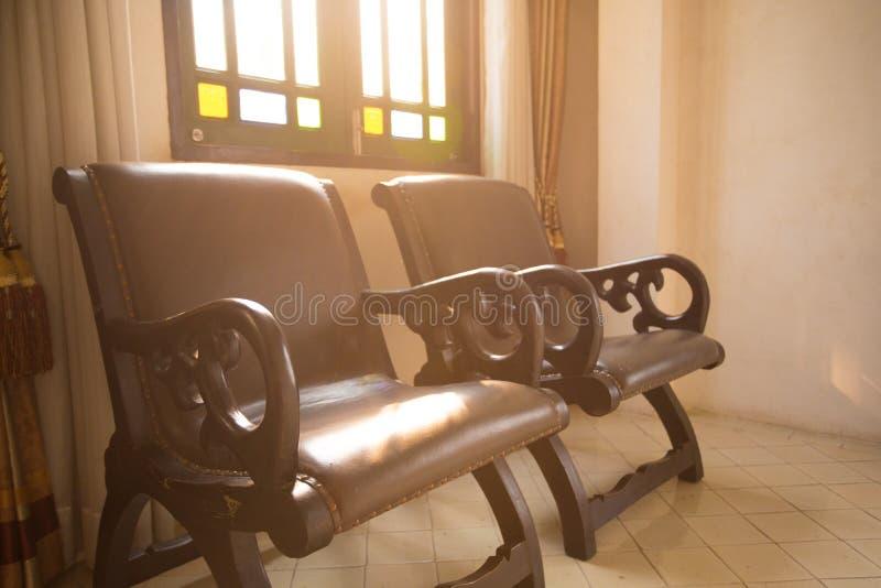 De koloniale oude stoel van het stijl uitstekende retro leer in de ruimte met stock foto