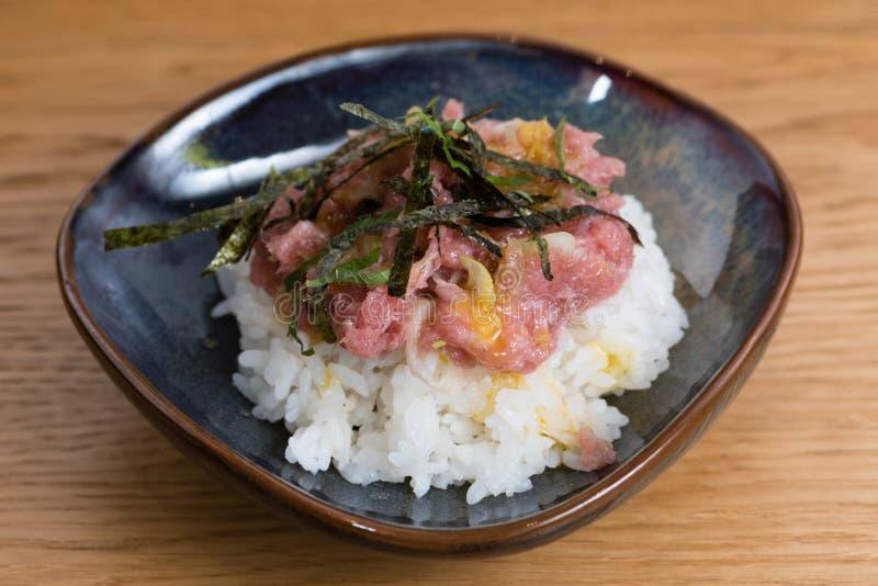 De kom met Kobe Beef tartare met gebraden norizeewier wordt gediend, eierdooier, hakte ui, over een bed van gestoomde witte rijst royalty-vrije stock afbeeldingen