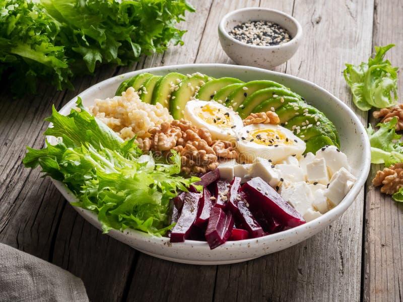 De kom van Boedha, evenwichtig voedsel, vegetarisch menu Oude houten donkere lijst, zijaanzicht Eieren, avocado, saladesla, bulgu royalty-vrije stock afbeelding