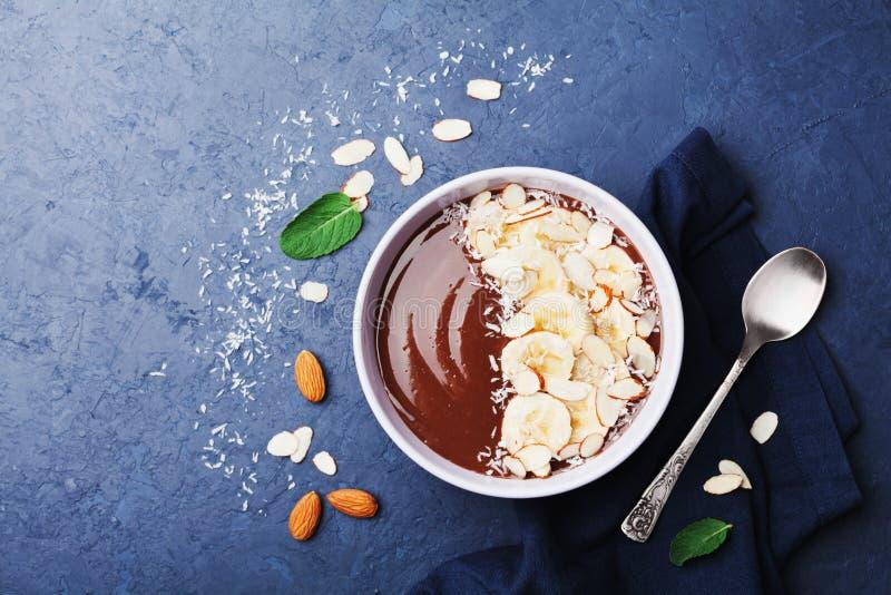 De kom van de de amandelkokosnoot van de chocoladebanaan smoothie op donkere de bovenkantmening van de steenlijst Gezond ontbijt  royalty-vrije stock afbeelding