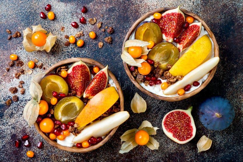 De kom van het dalingsontbijt met chocoladegranola, kokosnotenyoghurt en de herfst seizoengebonden vruchten en bessen Gezond Vege royalty-vrije stock afbeeldingen