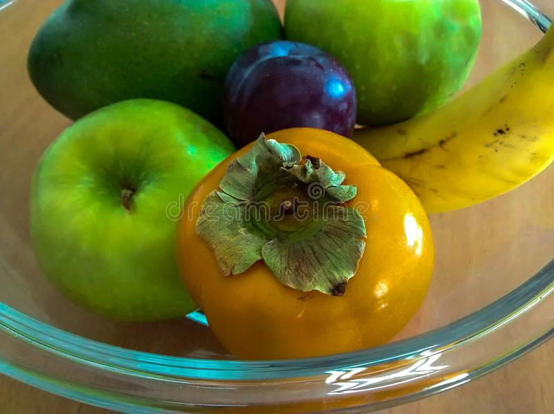 De kom van het glasfruit met dadelpruim, appelen, banaan, pruim en mango stock foto's