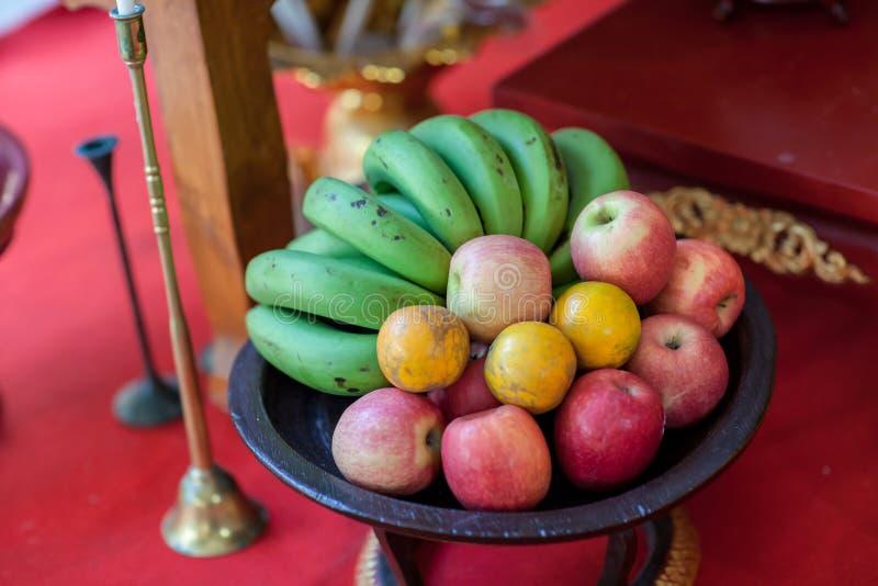 De kom van het metaalfruit op een houten oppervlakte sluit Bananen, sinaasappelen en appelen Mengeling van verse appel, banaan, s royalty-vrije stock afbeelding