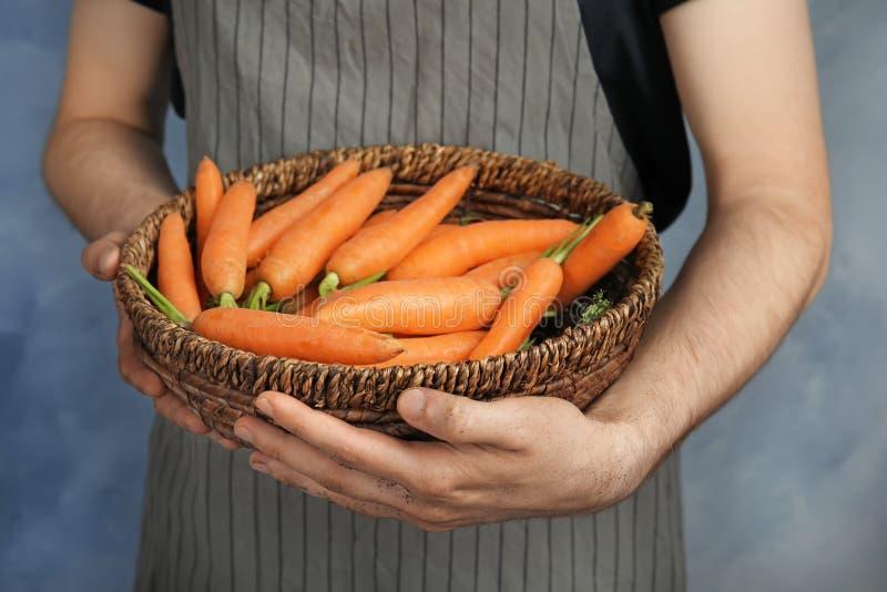 De kom van de jonge mensenholding met wortelen op kleurenachtergrond, close-up royalty-vrije stock afbeeldingen