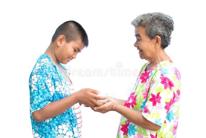 De kom van de jongensholding water en de bloem gieten neer aan oude handenvrouw op witte achtergrond stock afbeeldingen