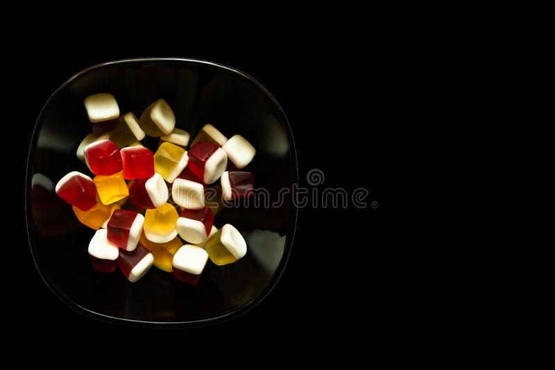 De kom van kleurrijke kubus vormde geleisuikergoed op zwarte achtergrond met exemplaarruimte stock foto
