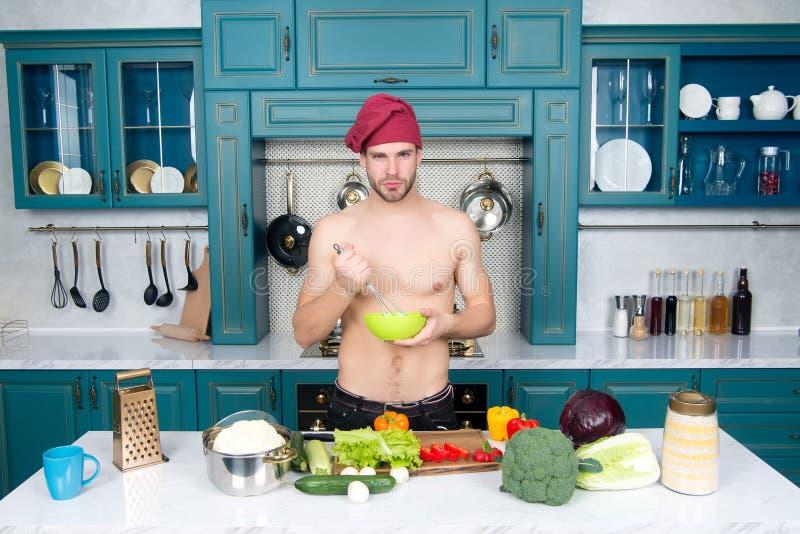 De kom van de mensengreep en zwaait bij lijst Chef-kok met spiertorsokok in keuken Groenten en werktuigen voor het koken van scho royalty-vrije stock afbeelding