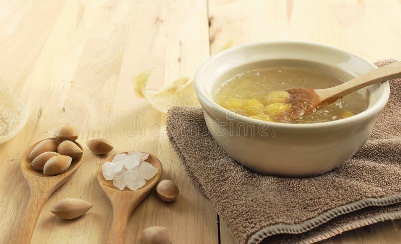 De kom van slikt van nest duidelijke soep en ginkgo zaden stock afbeelding