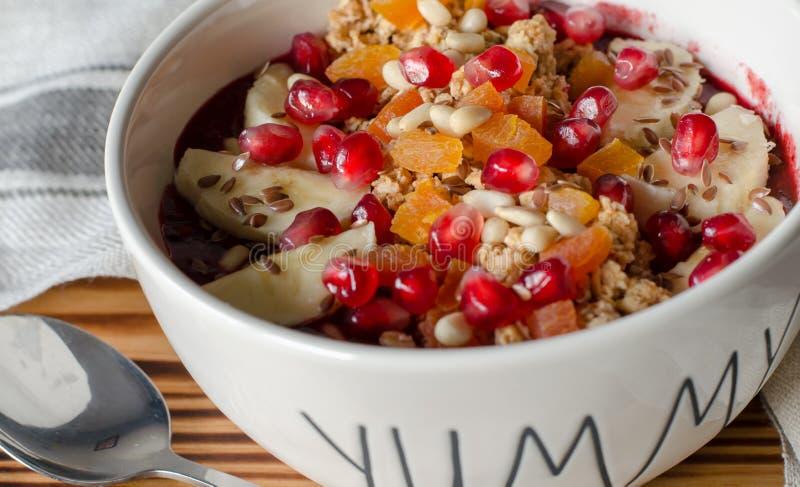 De kom van Smoothieacai met granaatappel, bananen, flaxseeds, cederzaden, droge abrikoos en granola wordt bedekt die Acaiontbijt  royalty-vrije stock afbeeldingen