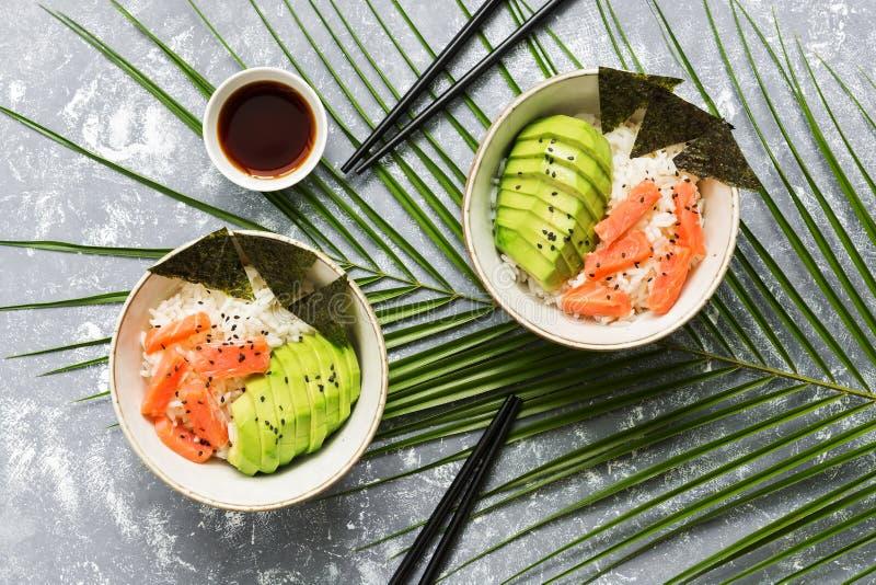 De kom van de zalmpor met rijst, nori, avocado, zwarte sesamzaden op een grijze die achtergrond met tropische bladeren wordt verf stock afbeeldingen