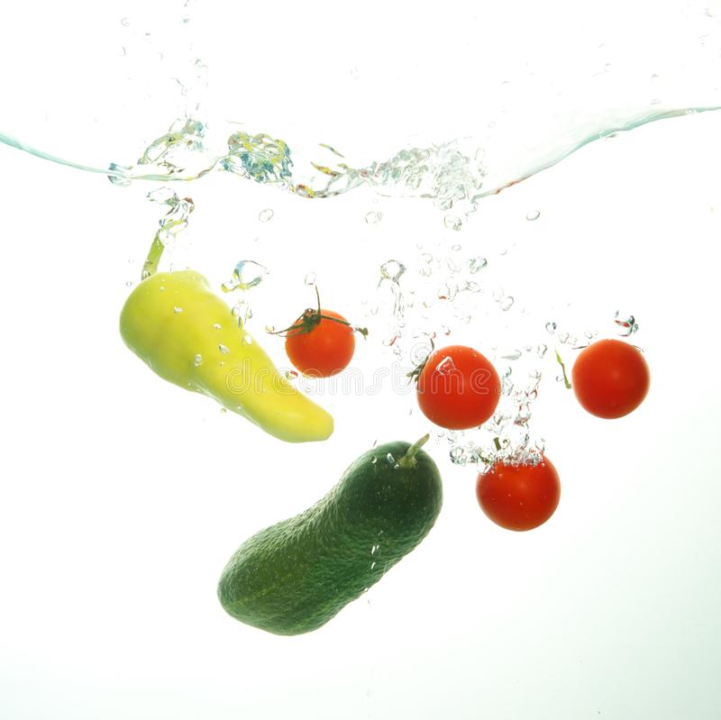 De komkommer van kersentomaten en groene papper onder water spash op w royalty-vrije stock fotografie