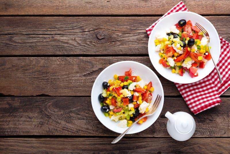 De kommen van de verse groentesalade van tomaten, graan, peper, olijven, selderie, groene ui en feta-kaas Gezond voedsel Dieetdin royalty-vrije stock fotografie