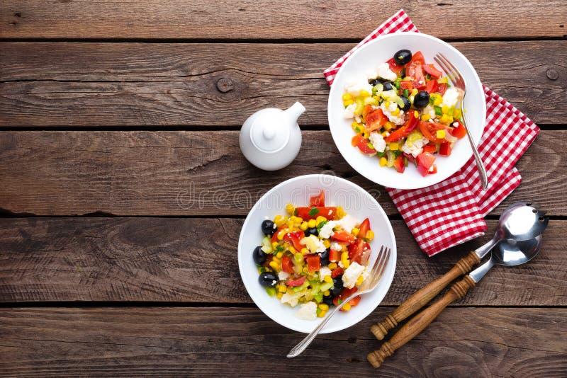 De kommen van de verse groentesalade van tomaten, graan, peper, olijven, selderie, groene ui en feta-kaas Gezond voedsel Dieetdin stock foto's