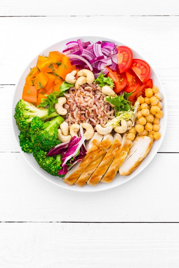 De komschotel van Boedha met kippenfilet, ongepelde rijst, peper, tomaat, broccoli, ui, kikkererwt, verse slasalade, cachou en wa royalty-vrije stock afbeeldingen