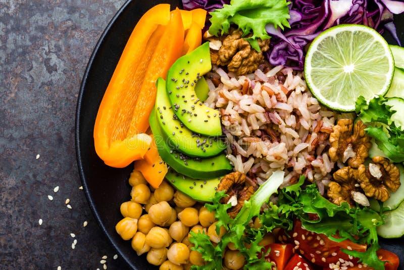 De komschotel van Boedha met ongepelde rijst, avocado, peper, tomaat, komkommer, rode kool, kikkererwt, verse slasalade en okkern royalty-vrije stock afbeelding