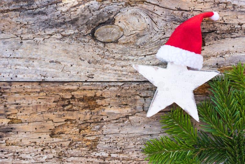 De komst en Kerstmis spelen decoratie met rode Santa Claus-hoed en groene spartak op houten achtergrond mee stock afbeelding