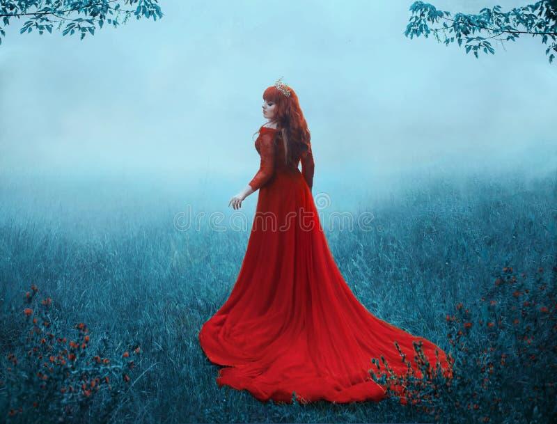 De Koningin in een luxueuze, dure, rode kleding, gangen in een dikke mist met een lange trein Een jong-haired meisje in gouden royalty-vrije stock foto