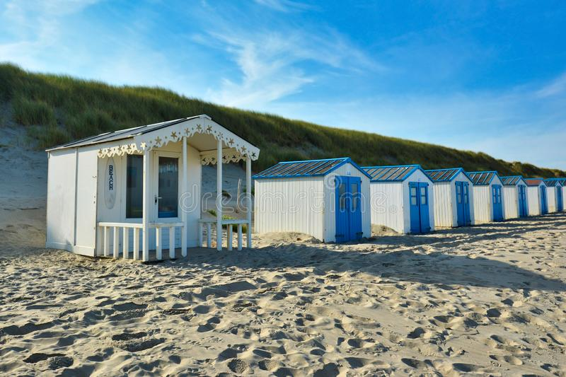 White and blue beach huts on island Texel in the Netherlands with blue sky on sunny day stock photo