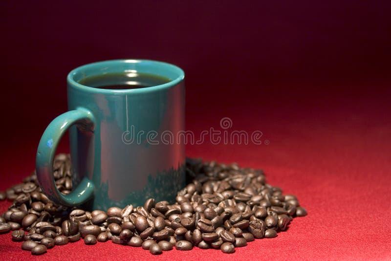 De kop en de bonen van de koffie stock foto's