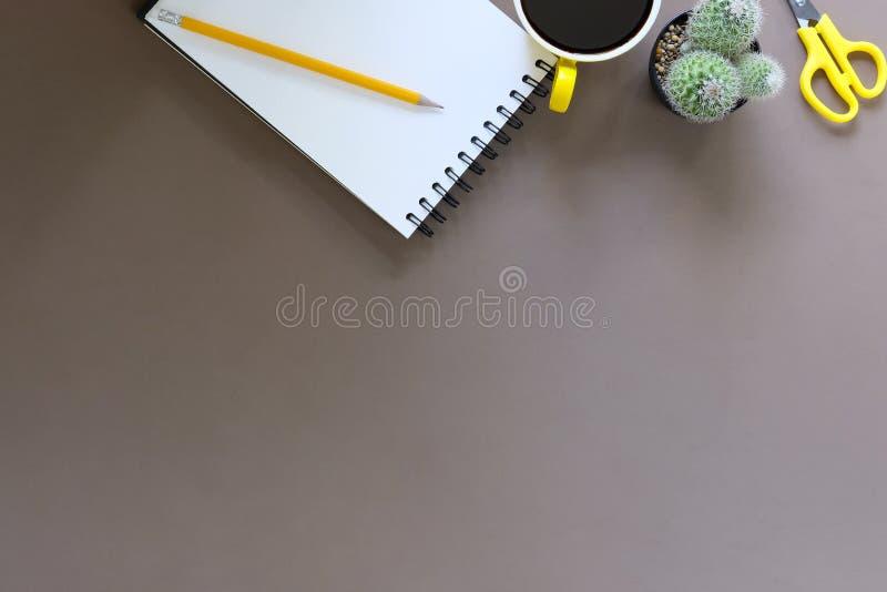 De kop en het potlood van de bureaukoffie met blocnotedocument op bruin Ta royalty-vrije stock foto's
