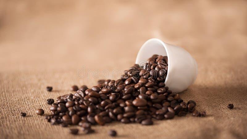 De kop giet koffiebonen op jute royalty-vrije stock afbeelding