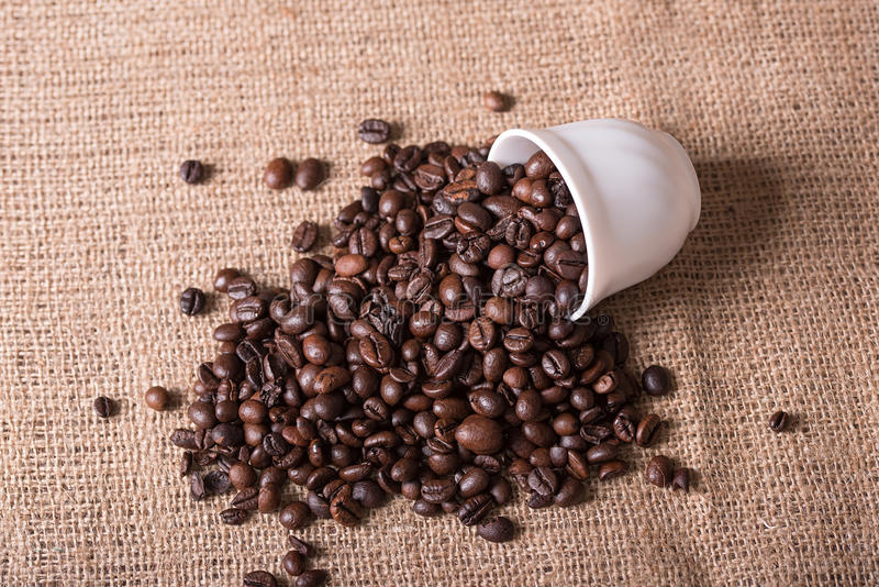 De kop giet koffiebonen op jute stock afbeeldingen