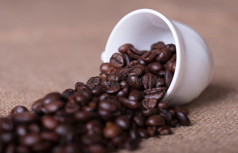 De kop giet koffiebonen op jute royalty-vrije stock afbeeldingen