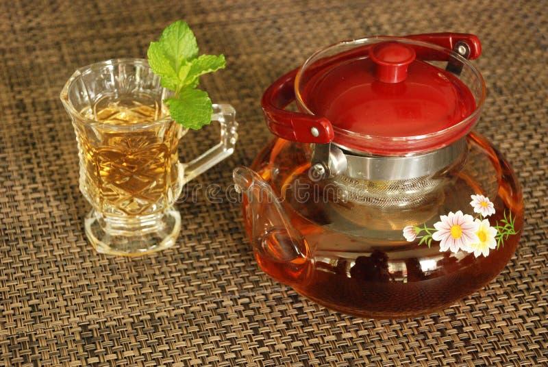 De kop thee met groen muntblad op de lijst diende te drinken stock foto