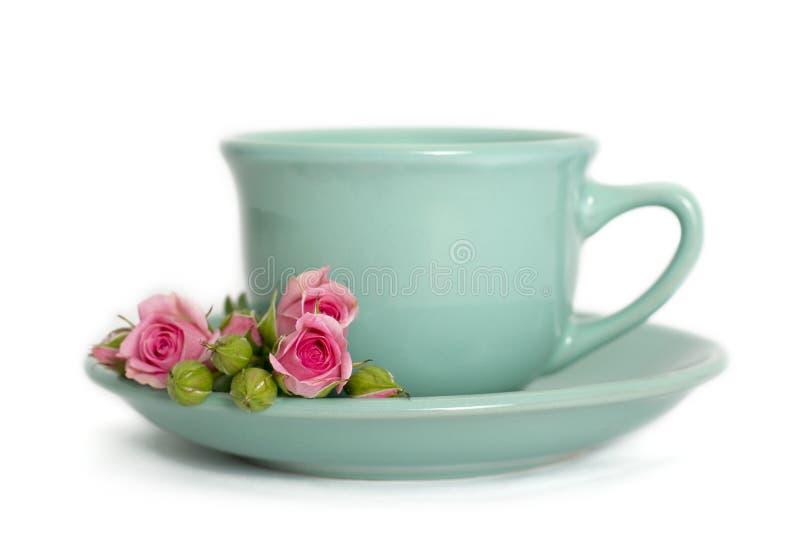 De kop thee met roze bloemen isoleted op wit stock fotografie