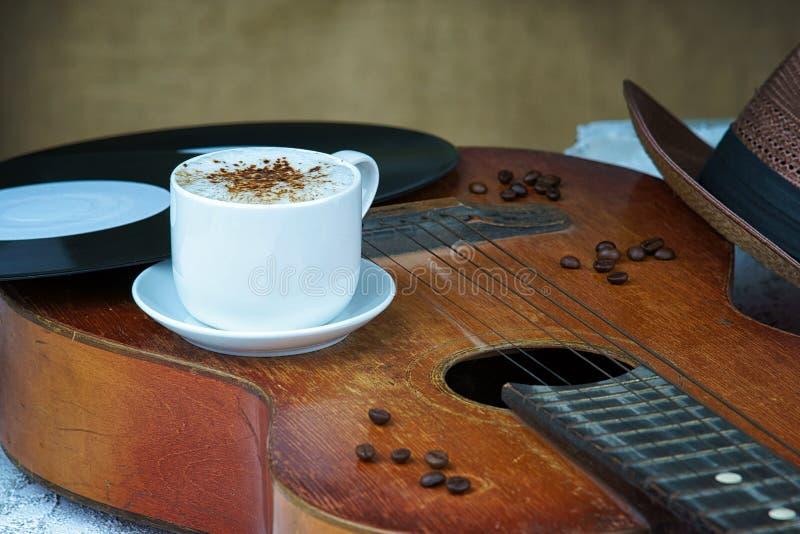 De kop van de cappuccinokoffie, gitaar, hoed en vinylplaat stock foto's