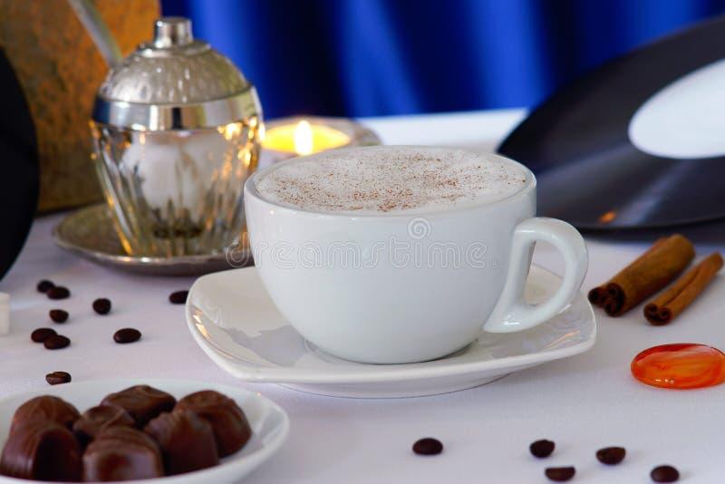 De kop van de cappuccinokoffie, koffiebonen, chocoladesuikergoed en kaars stock fotografie