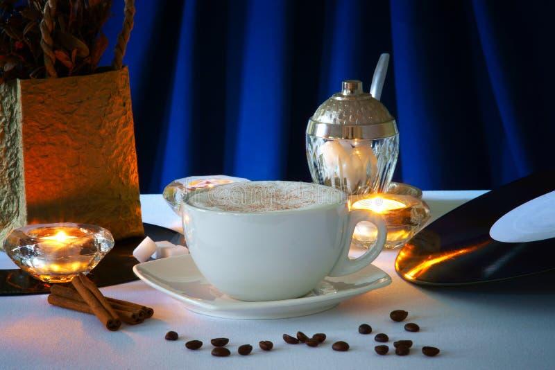 De kop van de cappuccinokoffie, koffiebonen en kaarsen royalty-vrije stock afbeeldingen