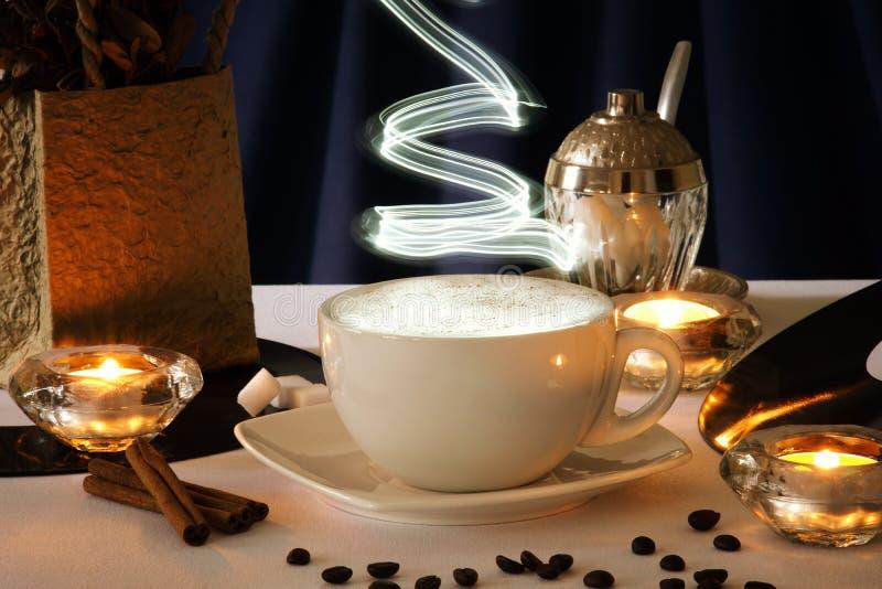 De kop van de cappuccinokoffie, koffiebonen en kaarsen royalty-vrije stock foto's