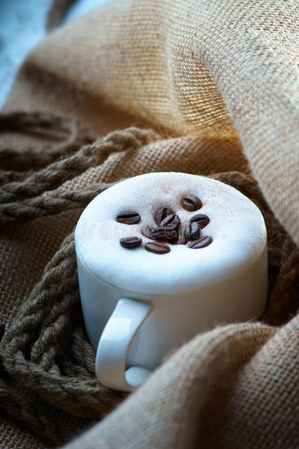 De kop van de cappuccinokoffie met koffiebonen op jutezak royalty-vrije stock foto