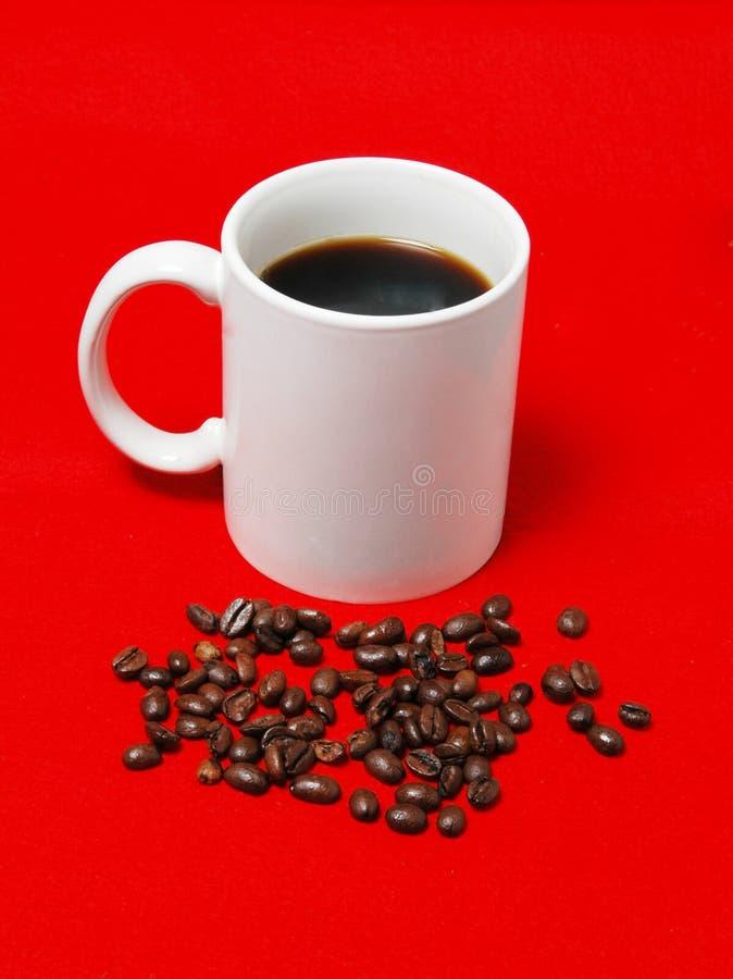 De kop van de koffie met bonen stock afbeeldingen