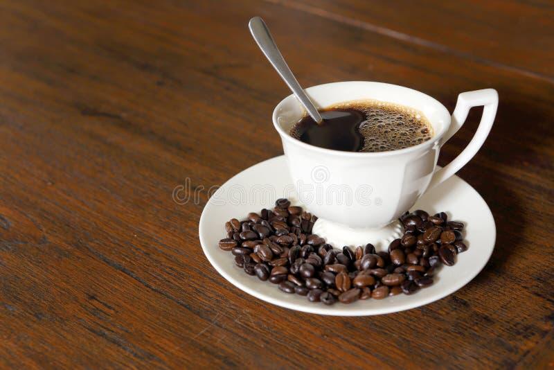 Download De Kop Van De Koffie Met De Bonen Van De Koffie Op Grungehout Stock Foto - Afbeelding bestaande uit gebrouwen, life: 29510832