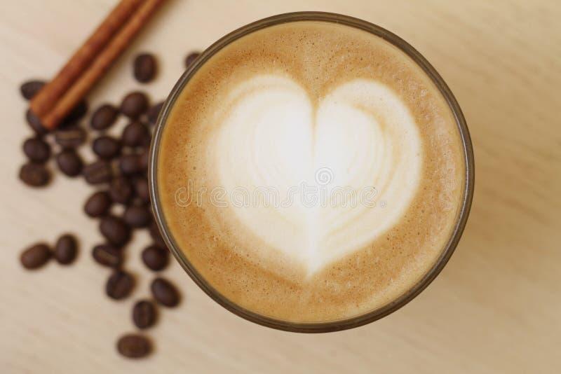 De kop van de koffie met melk en hartvorm stock afbeelding