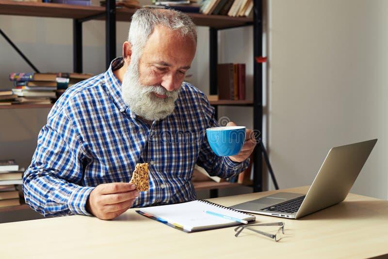 De kop van de zakenmanholding koffie en koekjes stock afbeelding