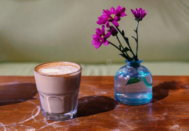 De kop van de glaskoffie met vlak-witte en roze bloemen in glasfles op het versleten opgepoetste tafelblad zijaanzicht royalty-vrije stock afbeelding