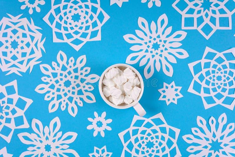 De kop van de handholding van hete chocolade met heemst en document sneeuwvlokken op blauwe achtergrond Hoogste mening royalty-vrije stock afbeeldingen