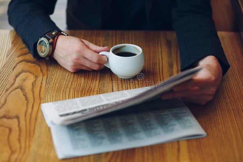 De kop van de het close-upholding van mensen` s handen van koffie en een krant stock foto's