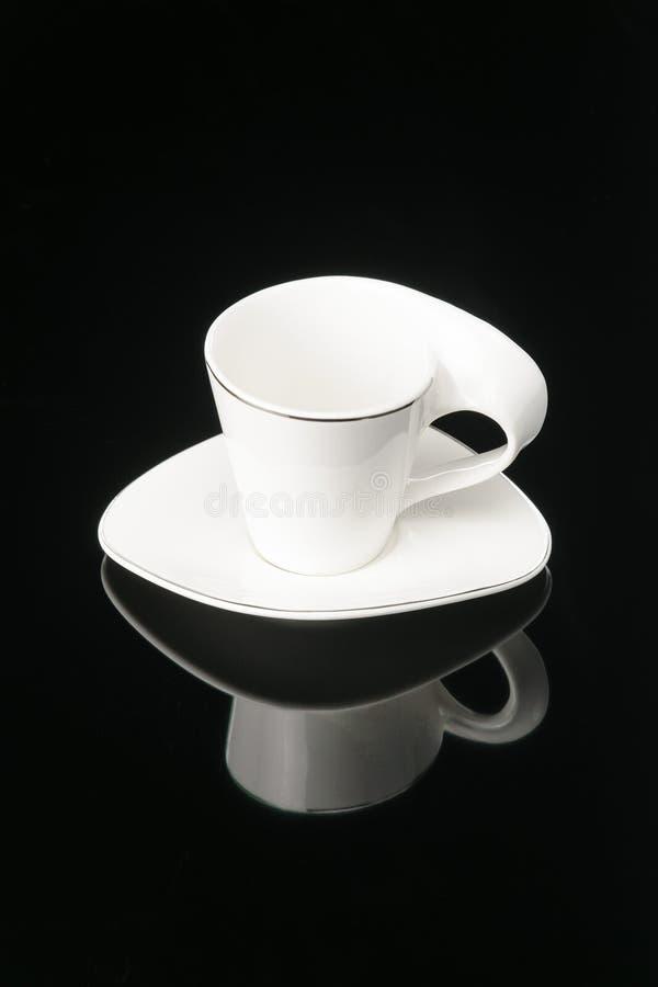 De kop van de het porseleinklei van de koffiethee met schotel op de zwarte spiegelachtergrond De ruimte van het exemplaar royalty-vrije stock foto's