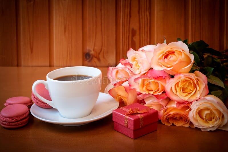 De kop van koffie, boeket van roze rozen bloeit en rode giftdoos stock afbeeldingen