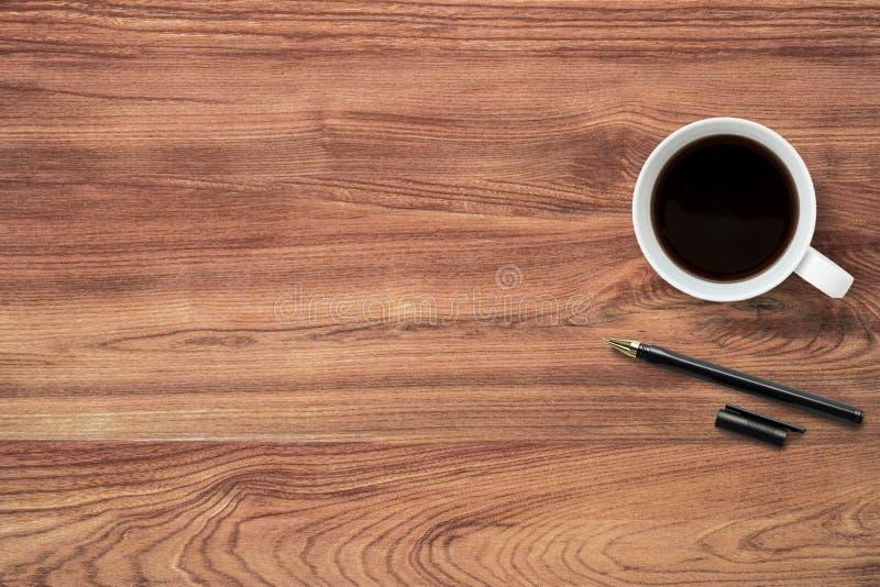 De kop van koffie en de pen zijn bovenop houten lijst De hoogste mening met vlakke exemplaarruimte, legt royalty-vrije stock fotografie