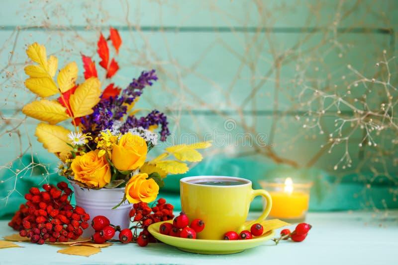 De kop van koffie, de herfst gaat en bloeit op een houten lijst weg Het stilleven van de herfst Selectieve nadruk stock foto