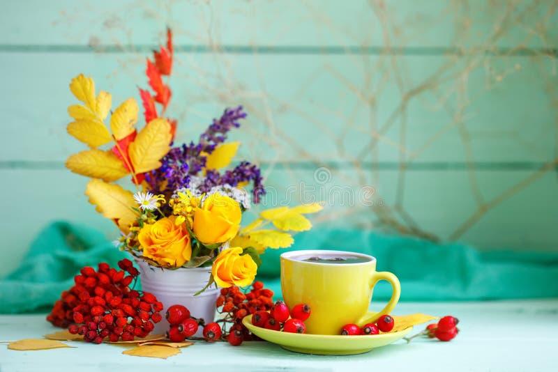 De kop van koffie, de herfst gaat en bloeit op een houten lijst weg Het stilleven van de herfst Selectieve nadruk royalty-vrije stock afbeelding