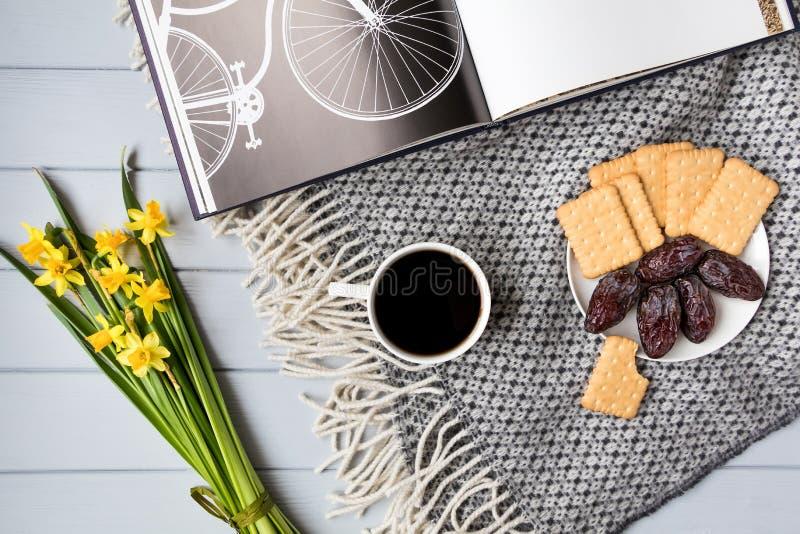 De kop van koffie, de koekjes van het crackerkoekje, datumvruchten, boek met fiets en gele narcis bloeit De hoogste vlakke mening royalty-vrije stock foto's