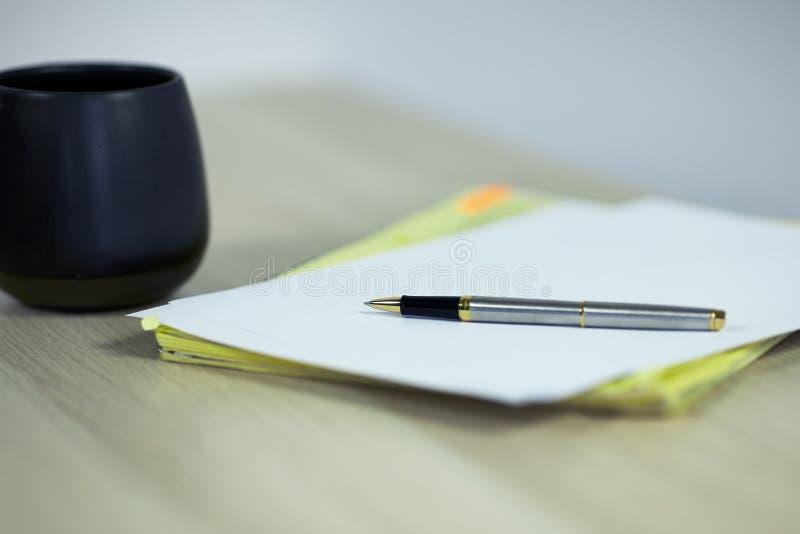 De kop van koffie of thee, het blad van document en de pen op lichte houten lijstachtergrond, sluiten omhoog royalty-vrije stock fotografie