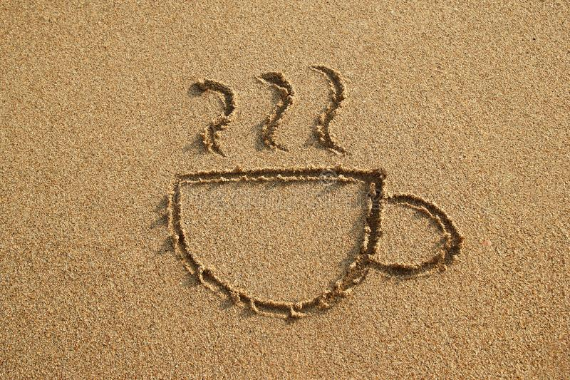 De kop van koffie wordt getrokken op een zandstrand op een zonsondergang royalty-vrije stock foto's